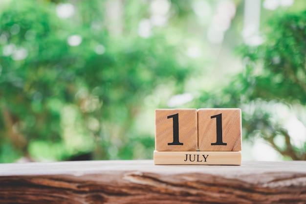 Hölzerner kalender am 11. juli auf weinleseholz