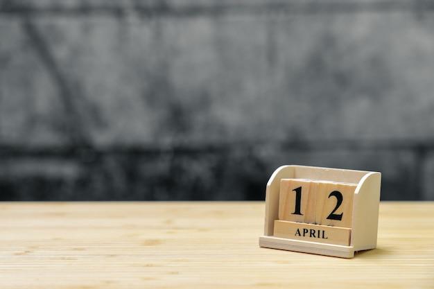 Hölzerner kalender am 12. april auf hölzernem abstraktem hintergrund der weinlese.