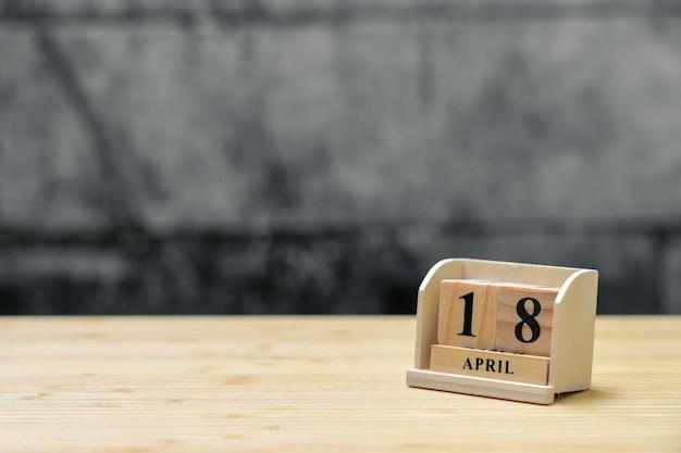 Hölzerner kalender am 18. april auf hölzernem abstraktem hintergrund der weinlese.