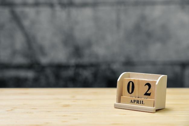 Hölzerner kalender am 2. april auf hölzernem abstraktem hintergrund der weinlese.