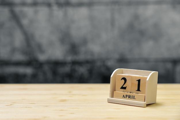 Hölzerner kalender am 21. april auf hölzernem abstraktem hintergrund der weinlese.