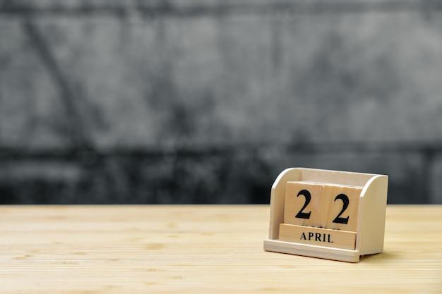 Hölzerner kalender am 22. april auf hölzernem abstraktem hintergrund der weinlese.