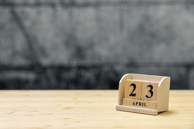 Hölzerner kalender am 23. april auf hölzernem abstraktem hintergrund der weinlese.