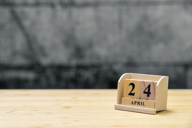 Hölzerner kalender am 24. april auf hölzernem abstraktem hintergrund der weinlese.