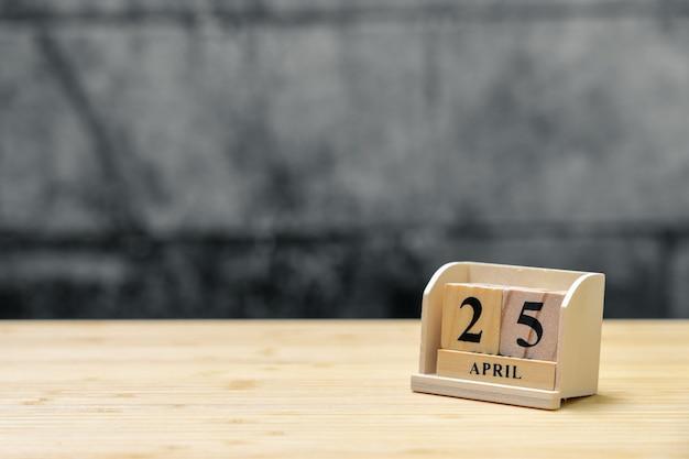 Hölzerner kalender am 25. april auf hölzernem abstraktem hintergrund der weinlese.