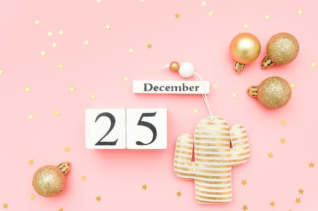 Hölzerner kalender am 25. dezember, goldtextilweihnachtskaktus und sternkonfettis auf rosa hintergrund.