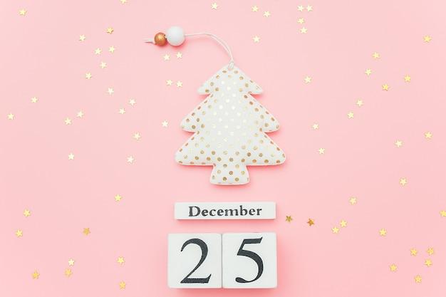 Hölzerner kalender am 25. dezember, textilweihnachtsbaum und sternkonfettis auf rosa