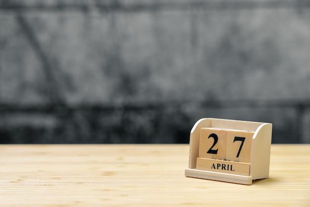 Hölzerner kalender am 27. april auf hölzernem abstraktem hintergrund der weinlese.