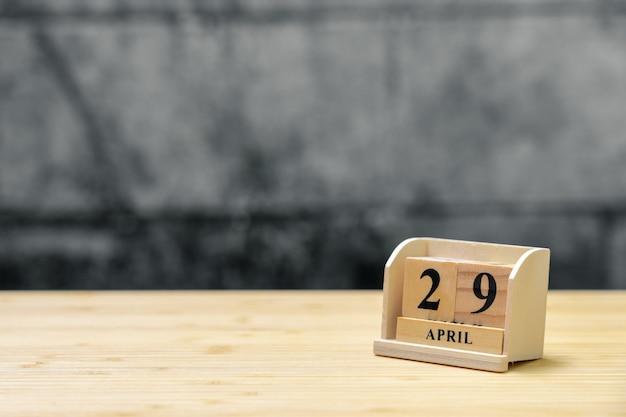 Hölzerner kalender am 29. april auf hölzernem abstraktem hintergrund der weinlese.