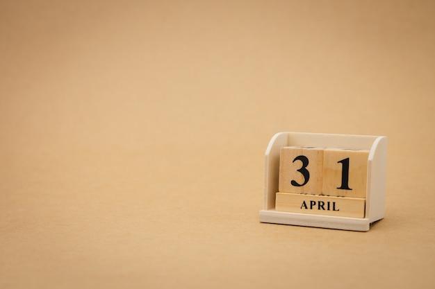 Hölzerner kalender am 31. april auf hölzernem abstraktem hintergrund der weinlese.