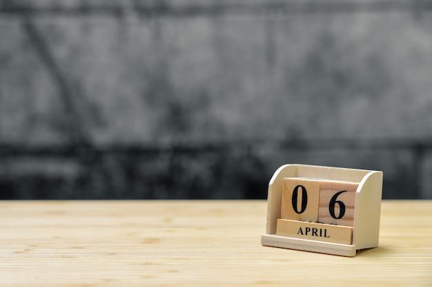 Hölzerner kalender am 6. april auf hölzernem abstraktem hintergrund der weinlese.