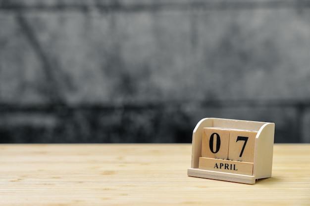 Hölzerner kalender am 7. april auf hölzernem abstraktem hintergrund der weinlese.
