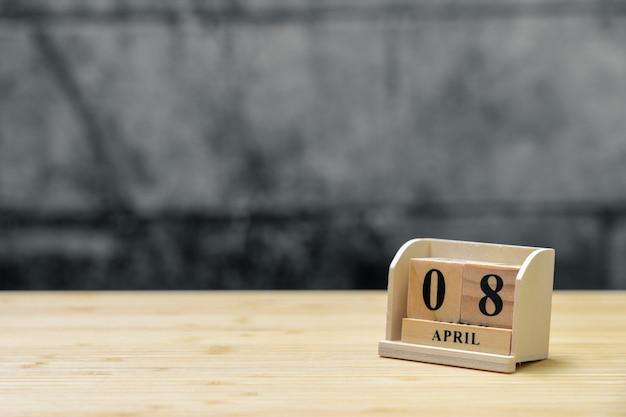 Hölzerner kalender am 8. april auf hölzernem abstraktem hintergrund der weinlese.