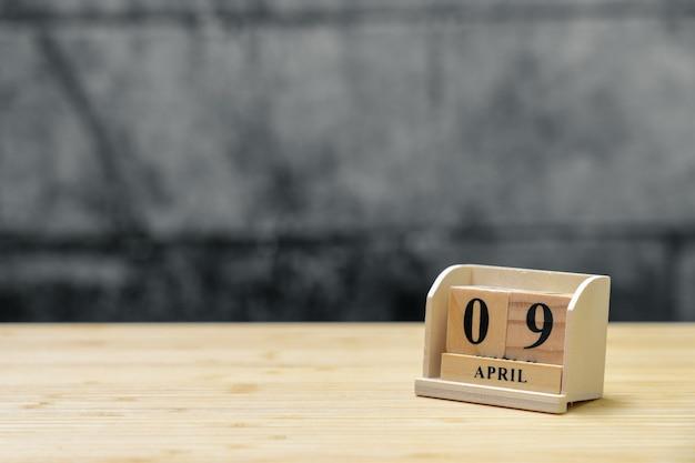 Hölzerner kalender am 9. april auf hölzernem abstraktem hintergrund der weinlese.