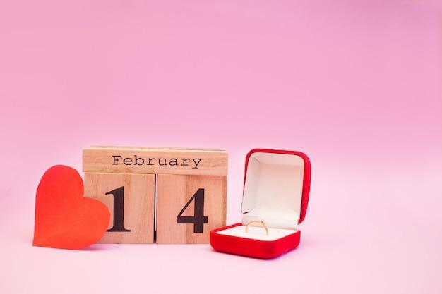 Hölzerner kalender auf einem rosa hintergrund mit roten herzen. valentinstag 14. februar