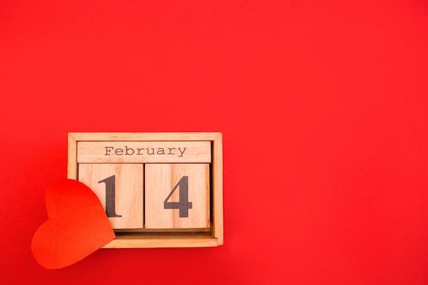 Hölzerner kalender auf einem roten hintergrund. valentinstag