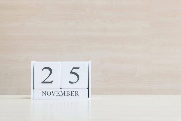 Hölzerner kalender der nahaufnahme mit schwarzem wort am 25. november auf hölzernem schreibtisch