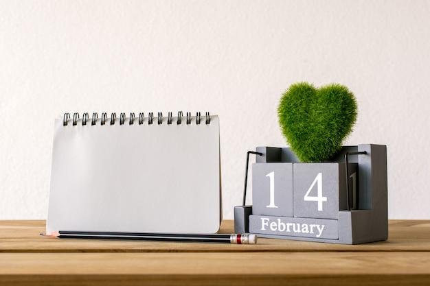 Hölzerner kalender der weinlese für den 14. februar mit grünem herzen