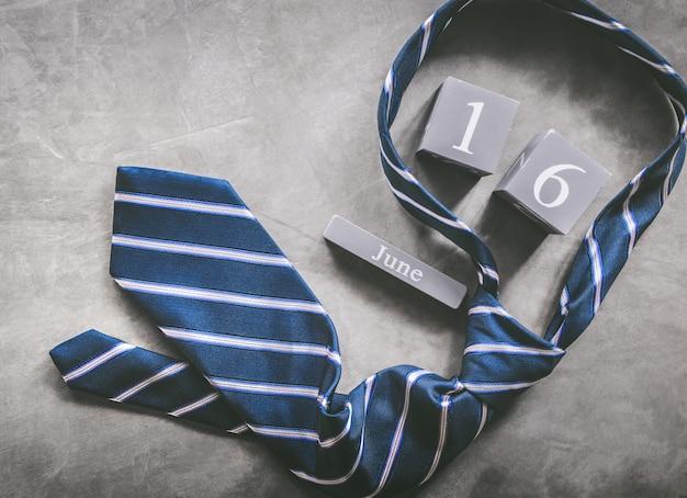 Hölzerner kalender der weinlese für den 16. juni mit krawatte glücklichem vatertagshintergrund