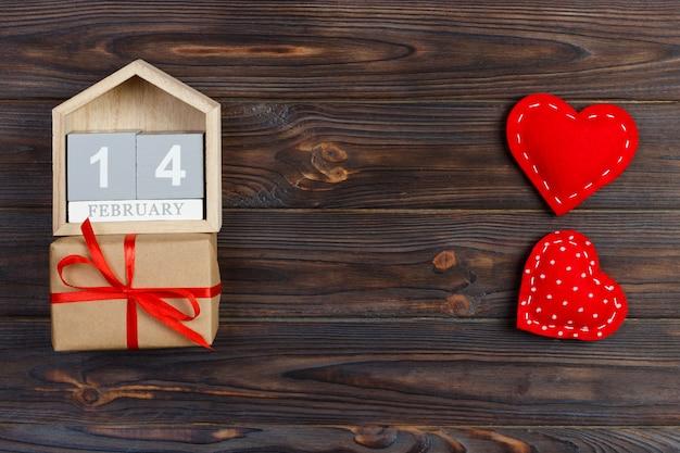Hölzerner kalender mit rotem herzen und geschenkbox
