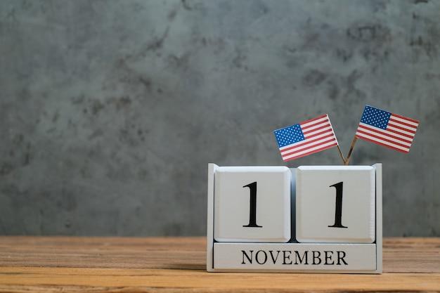 Hölzerner kalender vom 11. november mit amerikanischen miniaturflaggen. konzepte zur feier des weltveteranentages