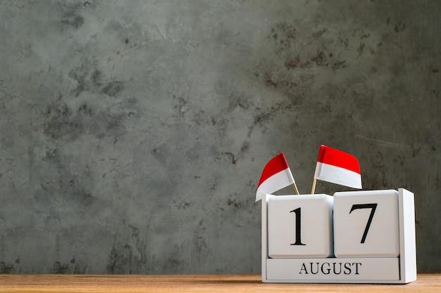 Hölzerner kalender vom 17. august mit miniaturflaggen von indonesien. indonesiens unabhängigkeitstag, nation holiday day und fröhliche feierkonzepte