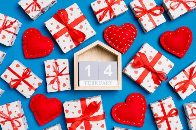 Hölzerner kalender, weiße geschenkboxen des feiertags und rote textilherzen auf blau