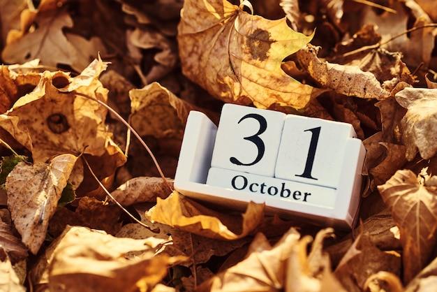 Hölzerner kalenderblock mit datum 31. oktober auf fallendem herbstlaub