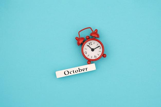 Hölzerner kalenderherbstmonat oktober und roter wecker auf blau