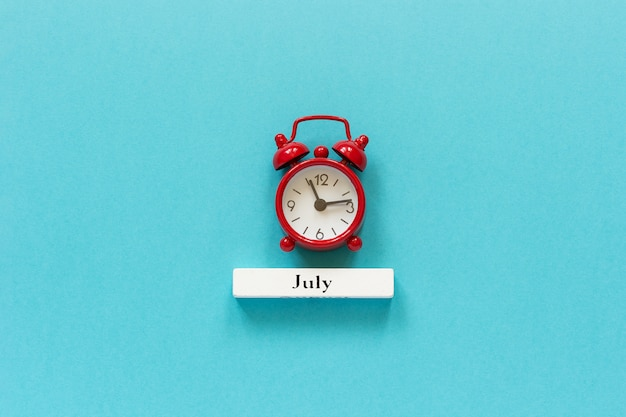Hölzerner kalendersommermonat juli und roter wecker auf hintergrund des blauen papiers.