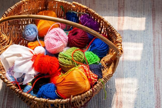 Hölzerner korb mit natürlichen bällen des regenbogens des garns auf einem alten traditionellen teppich.