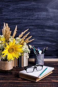 Hölzerner kreidebrettrahmen und vasenblumenstrauß auf der tabelle leer