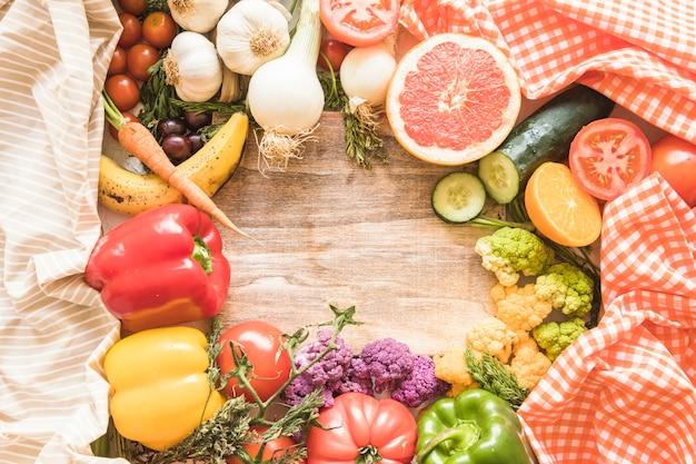 Hölzerner leerer rahmen umgeben mit gemüse und früchten
