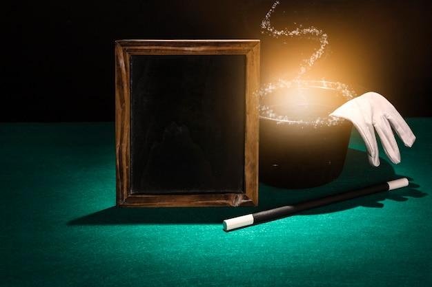 Hölzerner leerer rahmen; zauberstab und leuchtender zylinder mit weißen handschuhen auf grünem hintergrund