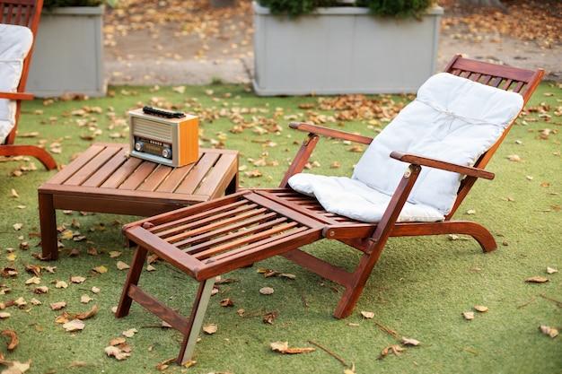 Hölzerner liegestuhl auf grünem sommerrasen auf picknick