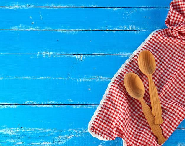 Hölzerner löffel auf einem roten geschirrtuch, blauer hintergrund