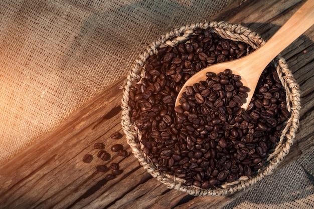 Hölzerner löffel der kaffeebohnen über korb von kaffeebohnen. mattart, weinleseart.