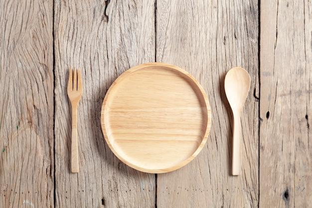 Hölzerner löffel und hölzerne platte auf altem hölzernem tabellenhintergrund