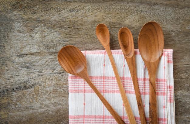 Hölzerner löffel und küchengeschirr stellten verschiedene größen des kaffeelöffels auf napery auf speisetische ein
