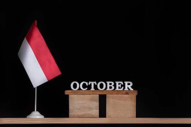 Hölzerner oktoberkalender mit polnischer flagge auf schwarzer oberfläche. feiertage in polen im oktober.