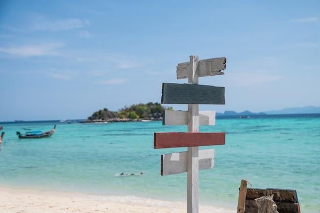 Hölzerner pfeilwegweiser auf weißem strand mit tropischem meer