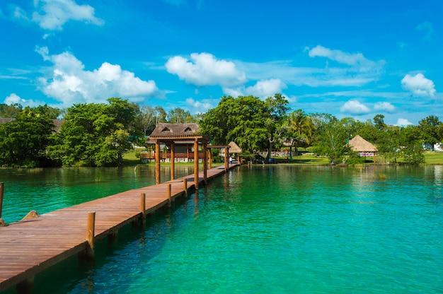 Hölzerner pier in der lagune der sieben farben mit schöner landschaft. das kristallklare wasser der bacalar lagune, quintana roo, mexiko.