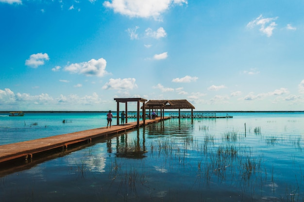 Hölzerner pier in der lagune der sieben farben mit schöner landschaft. leute, die das haarscharfe wasser der bacalar-lagune, quintana roo, mexiko genießen