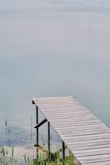 Hölzerner pier oder anlegestelle auf blauem seesonnenuntergang und himmelreflexionswasser. alter kleiner see