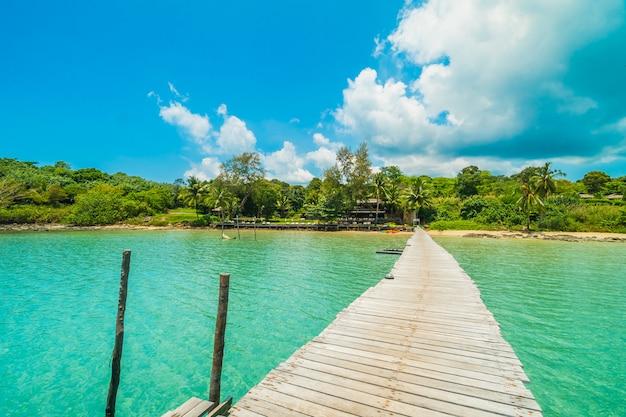 Hölzerner pier oder brücke mit tropischem strand