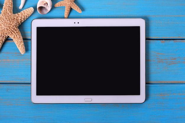 Hölzerner plattform-sommerhintergrund des blauen strandes des tablet-computers