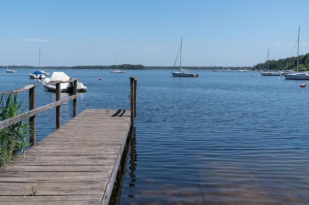 Hölzerner ponton in lacanau-blauem seewasser mit boot in frankreich
