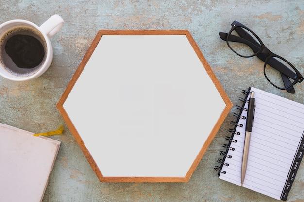 Hölzerner rahmen des weißen hexagons mit kaffee und schreibwaren auf schmutzhintergrund