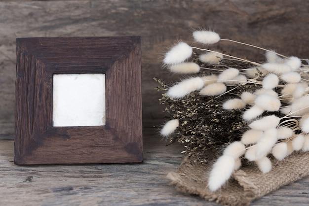 Hölzerner rahmen und trockener blumenblumenstrauß auf schmutzholztisch