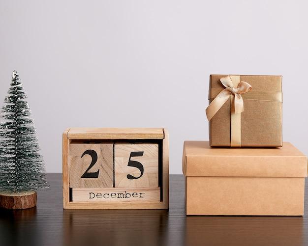 Hölzerner retro- kalender von den blöcken, vom weihnachtsdekorativen baum und von den pappschachteln mit geschenken